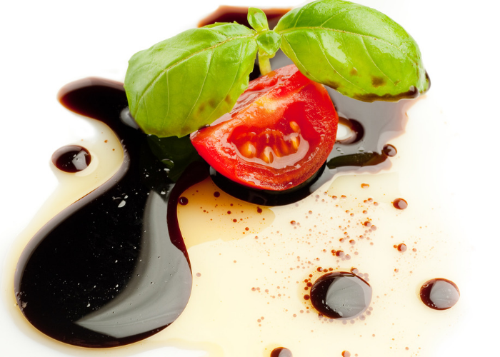 Close up of piece of cherry tomato and basil leaf on balsamic vinegar and olive oil