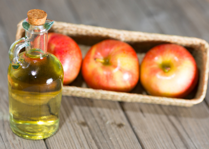 Bottle of apple cider vinegar with three apples in a basket in the background