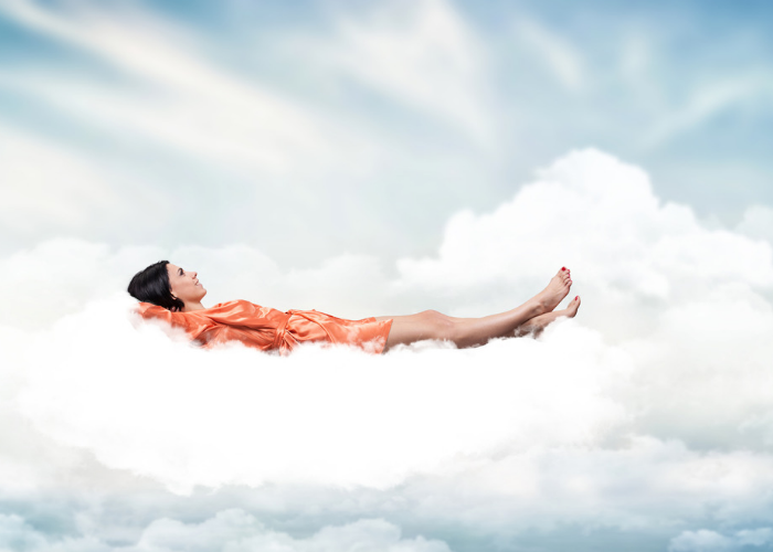 Woman lying on clouds in a dream