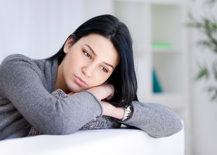 Woman with depression leaning on her hands