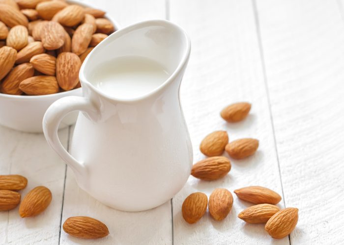 A jug of non-dairy almond milk, a bowl of almonds, and almonds scattered on the table around the jug