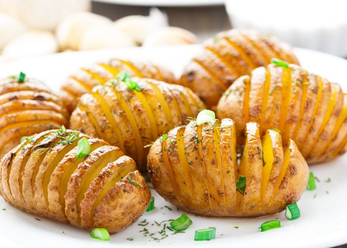 Roasted accordion potatoes on a white dish sprinkled with parsley