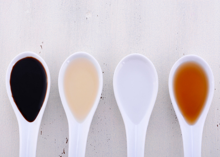 Four soup spoons holding different vinegars