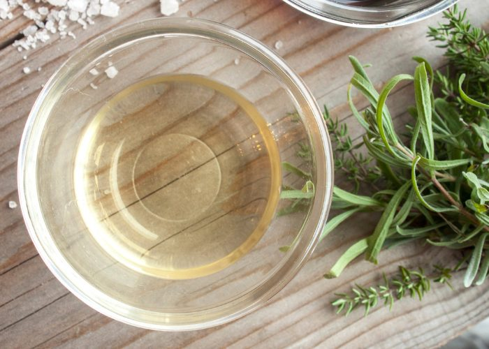 Small glass dish with white distilled vinegar in it next to herbs and salt