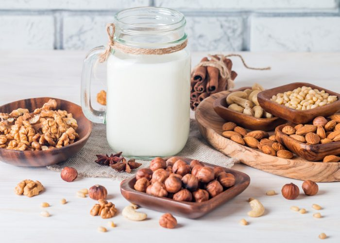 A mason jar filled with non-dairy milk and wooden dishes filled with nuts like walnuts, macadamias, cashews, and almonds around the jar on a white table