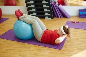 Woman doing ab exercises with ball using a yoga mat