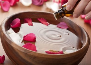 Woman adding aromatherapy oil to a bowl of water with rose petals