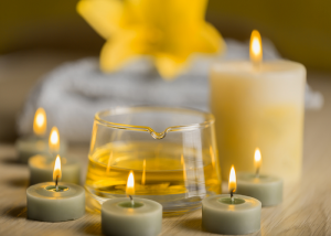 A display of aromatherapy tea candles with a bigger aromatherapy candle in the background and a bowl of aromatherapy oil