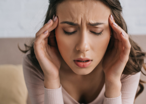 Woman holding her temples due to a painful headache