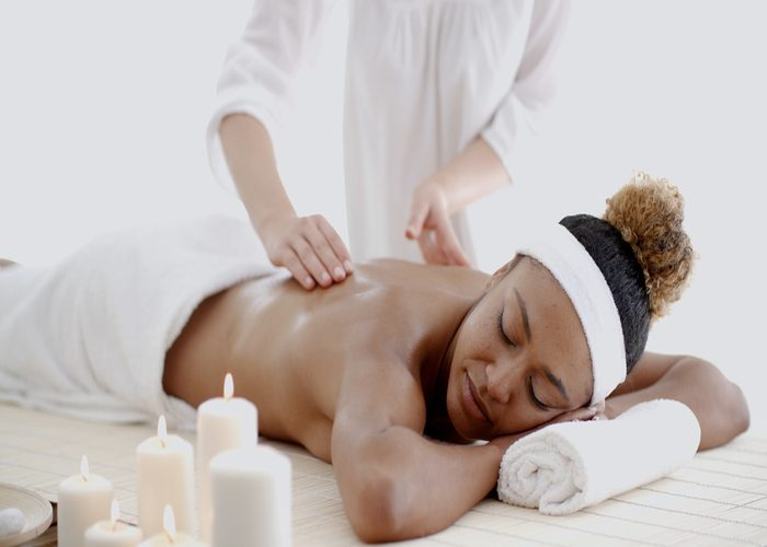 Woman getting a massage with aromatherapy oils and candles
