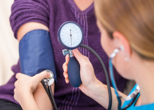 Doctor taking a female patient's blood pressure