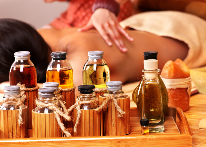 Bottles of aromatherapy oils in a massage studio with a woman getting a massage with them in the background.