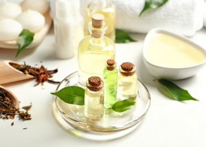 A plate featuring tea tree aromatherapy oil bottles of different sizes with aromatherapy creams and candles in the background