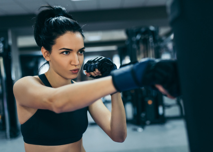 Woman in a gym practicing kickboxing punches on a punching bag