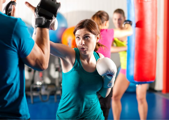 Woman in a kickboxing class practicing with boxing pads