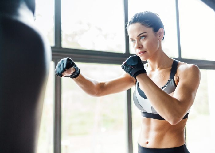 Fit woman with abs practicing kickboxing on a punching bag in a bright gym