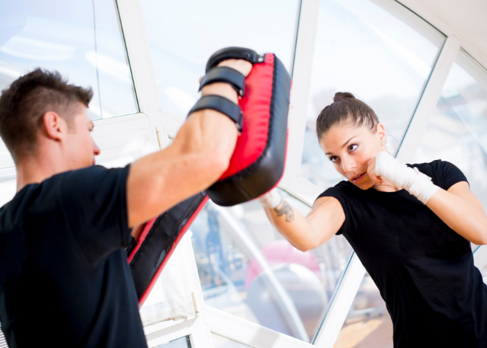 Young fit female doing kickboxing exercises with an instructor