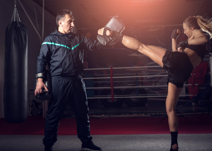 A fit blonde woman doing a high side kick with her kickboxing instructor holding a training pad