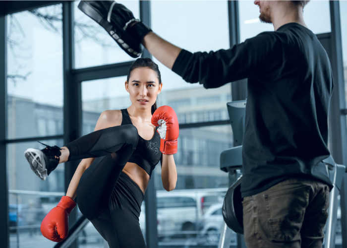 Asian woman in a gym with her kickboxing instructor attempting a high side kick