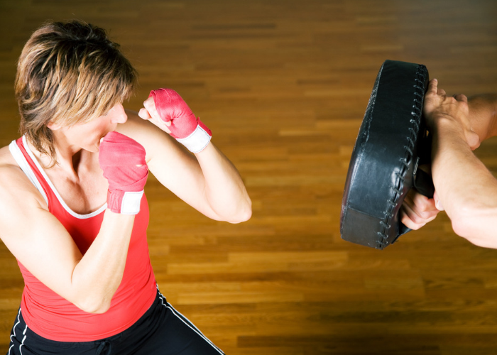 Top down view of fit woman with short hair practicing kickboxing with an instructor