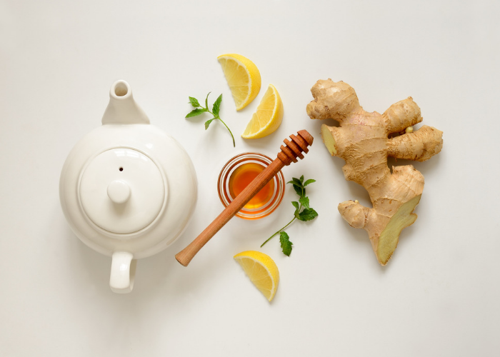 A flat lay featuring a tea pot, honey pot, slices of lemon, and ginger.