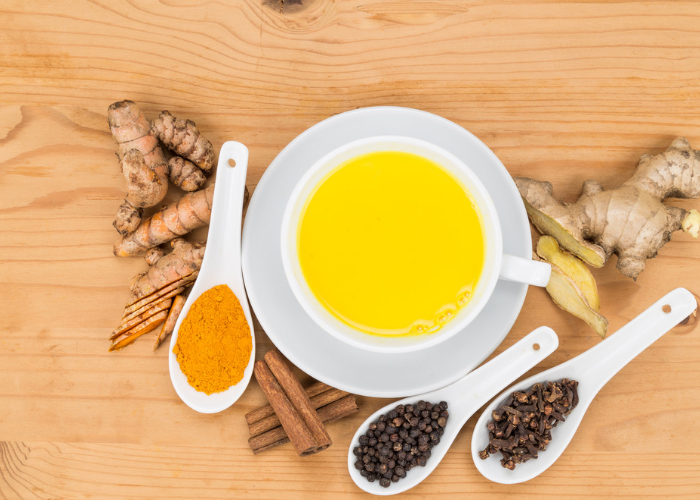 A large cup of turmeric tea  surrounded by spoons of turmeric tea ingredients.
