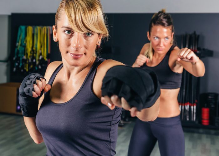 Two women practicing jabs in a kickboxing class