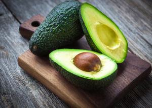 A whole avocado and a halved avocado on a wooden board
