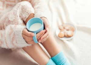 A woman sitting on her bed holding a cup of warm milk
