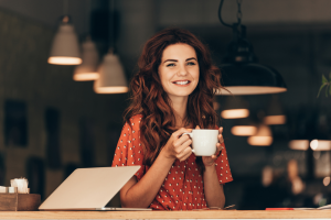 Woman smiling and drinking coffee at a cafe as she works