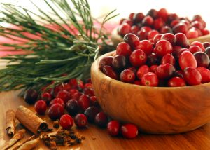 Dozens of cranberries piled high in small wooden bowls