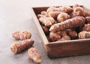 A pile of Jerusalem artichokes in a wooden container