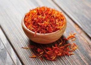 A bowl of saffron on a wooden table