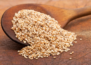 A wooden spoon filled with sesame seeds