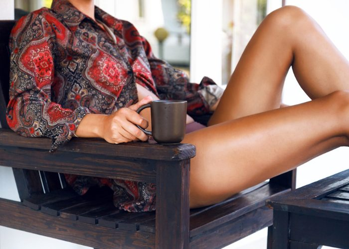 Woman sitting outdoors relaxing and drinking a cup of detox tea