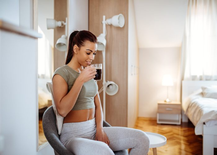 Woman sitting in her bedroom post-workout drinking a cup of detox tea