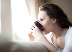 Woman staring out the window drinking a cup of detox tea