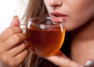 A woman drinking a cup of teatox
