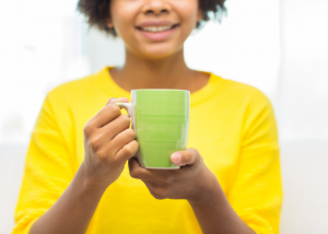 Woman holding up a cup of detox tea ready to drink it