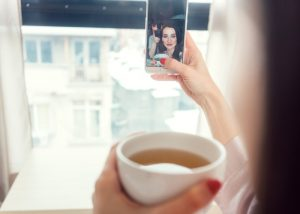 Woman taking a selfie of herself drinking a cup of detox tea