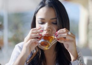 Woman sipping teaxtox from a cup
