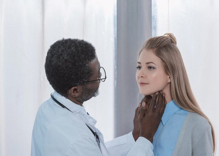 Doctor examining a patient's thyroids using his hands