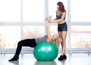 Women doing an exercise ball workout with a trainer in the gym