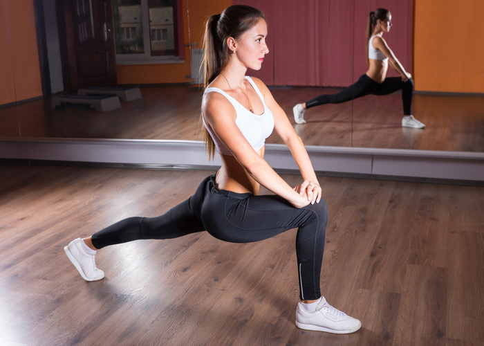 Woman doing a forward lunge in a dance studio