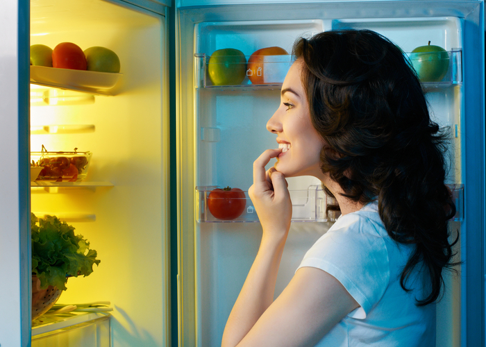 Woman trying to find a late night snack in her fridge