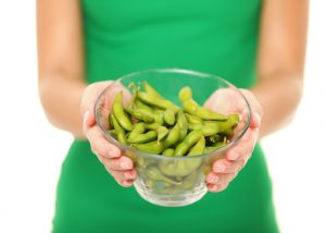A woman holding a bowl of freshly cooked edamame ready to eat as a healthy late night snack