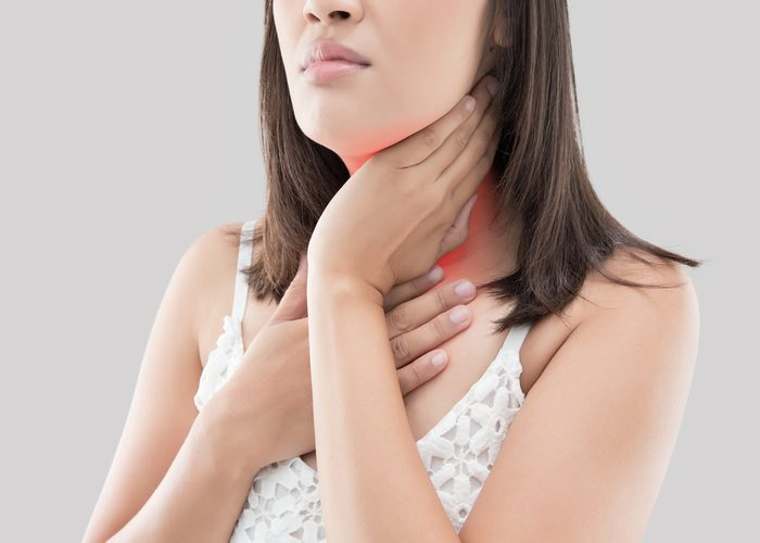 Woman holding her neck in pain due to thyroid disease