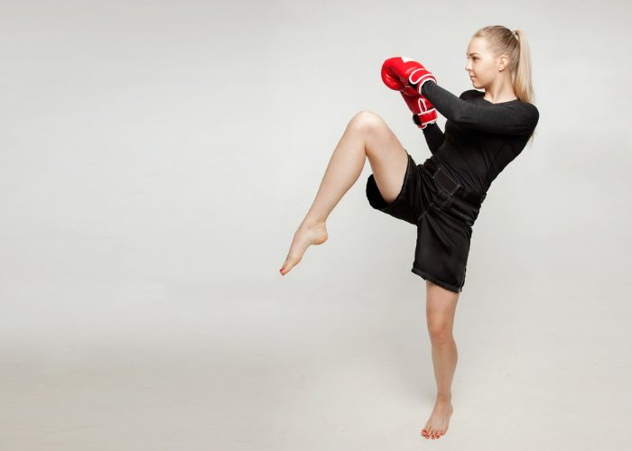 Young blonde woman practicing kickboxing against a plain wall