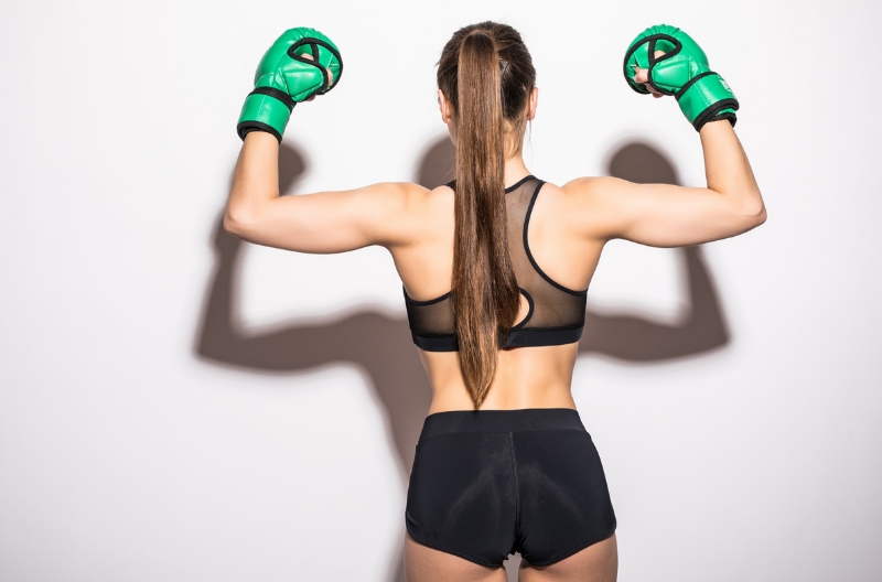 back view of a fit kickboxing girl wearing boxing gloves with her arms raised