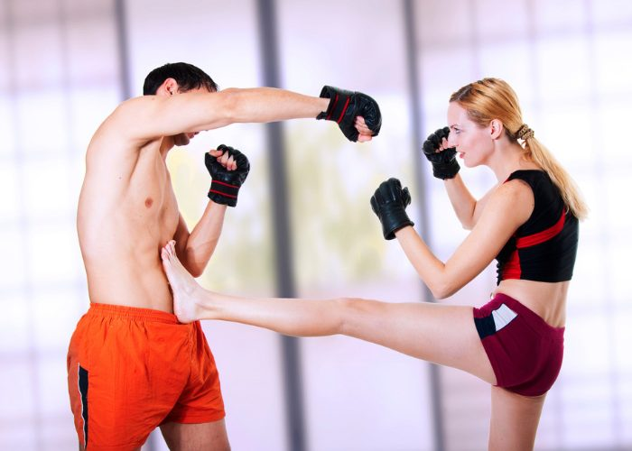 A woman practicing her kickboxing front kick against a male opponent